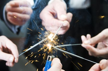 igniting: Lighter flame igniting spark sticks on new years evening
