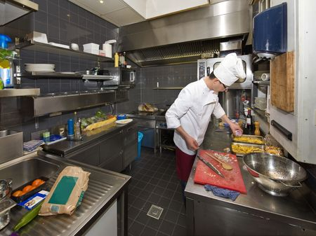 A chef in a profesional kitchen, preparing dinner photo