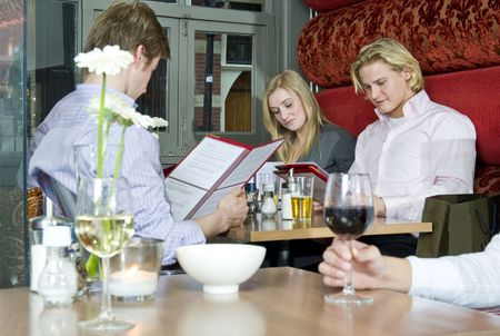 A group of people looking at the menu in a restaurant photo