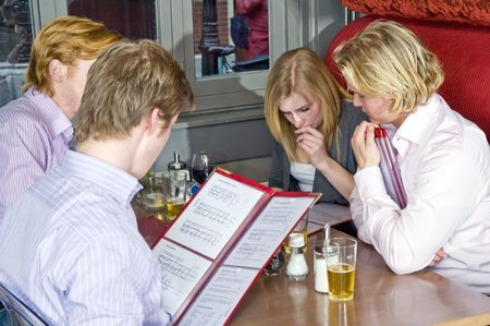 whine: a group of four people chosing dishes from the menu in a restaurant Stock Photo