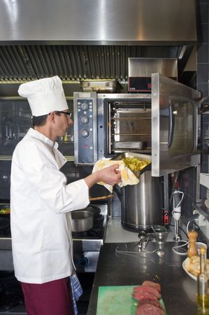 oven tray: A chef putting a tray of potatoes in a professional oven