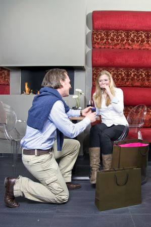 A man proposing to a woman in front of a restaurant fireplace photo