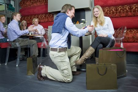 A youngwoman accepting her boyfriends proposal, whilst the other guests at a restarant applaud the young couple photo