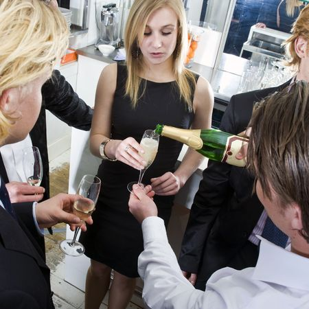 refilling: Waiter, refilling champagne glasses from the bottle in a bar on New years eve