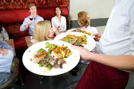 식당에서 저녁 식사를하는 친구들에게 식사를 제공하는 웨이터 스톡 콘텐츠