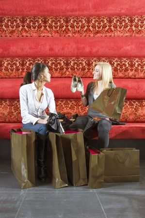 two young women showing their recent purchases to one another photo