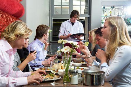 웨이터가 레스토랑에서 저녁 식사 손님들의 주문을 받는다. 스톡 콘텐츠