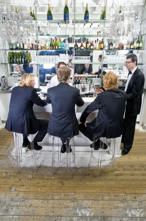 party outfit: four customers and a barkeeper sitting, standing, talking and drinking at a bar Stock Photo