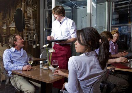 meseros: tomar las �rdenes de un cliente en un restaurante de camarero Foto de archivo