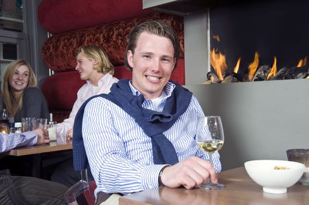 A posh looking man with his sweater around his neck and a glass of white wine in his hand sitting at a restaurant table in front of the fireplace Stock Photo - 6484887