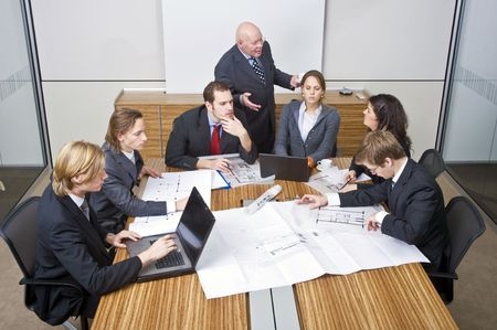 architectural firm: A business team going over the design changes at a corporate architectural firm