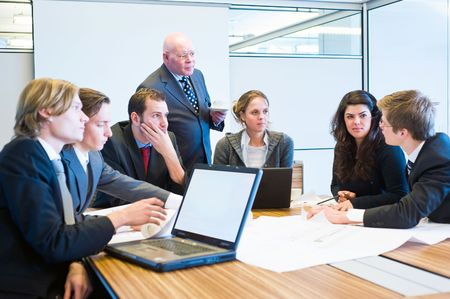 The youngest employee making a suggestion during a team meeting, and everybody, including the senior executive (boss) listens Stock Photo - 6484057