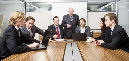 Seven people in a cubicle, preparing for a management team meeting Stock Photo - 6484046