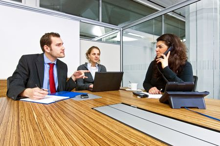 calling businessman: A small business team in a cubicle conference room during a meeting
