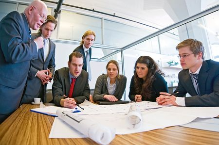 Group of seven designers discussing blueprints in a conference room. Stock Photo - 6484001