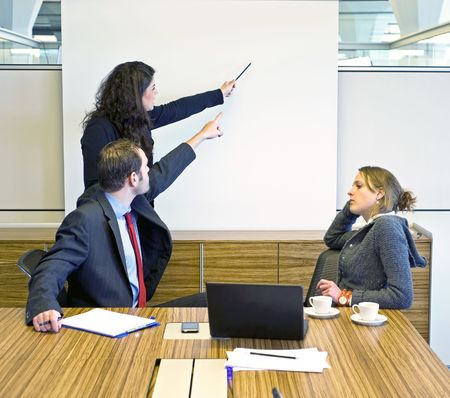 convincing: Two colleagues pointing at a presentation screen, trying to convince a bored looking businesswoman