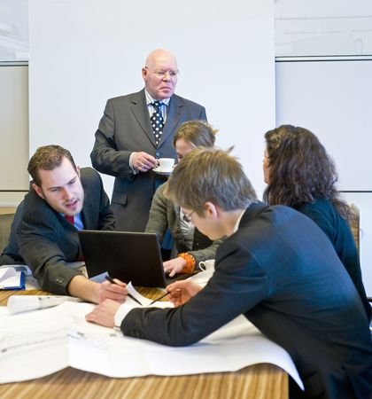 hectic: A hectic meeting, with five people working frantically on a design Stock Photo