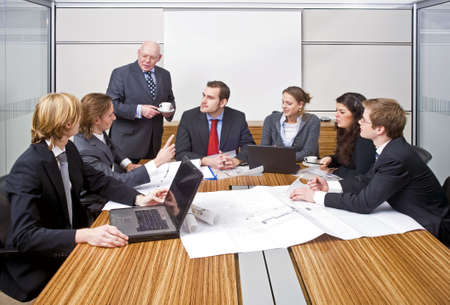 A group of six junior associates during a management team meeting with a senior manager photo