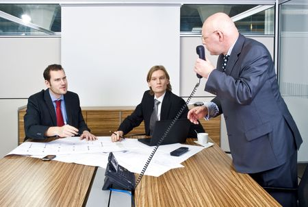 handing over: A business meeting with two young associates and a senior manager discussing plans and talking to a client on the phone Stock Photo