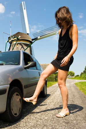 Young woman kicking angrily at the tire of her broken car on a rural road on a beautiful summer day Stock Photo - 6484074