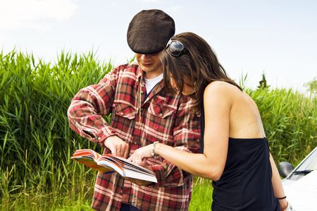 directional: Young woman asking a farmer for advice on where to go, consulting a guide book Stock Photo