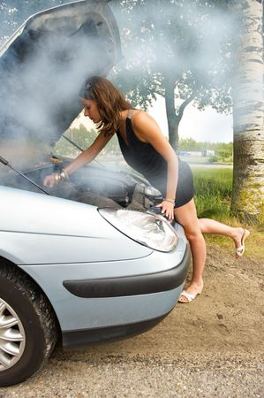 Young woman bending over the blown engine of her car, looking at the oil, whilst smoke is coming from under the hood photo