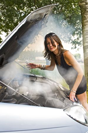 trouble: Young woman waiving through the thick smoke coming from the blown engine of her car, looking at the camera
