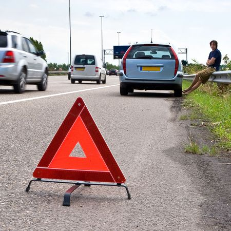 bending down: Man waiting outside of his broken car on the curb of a busy motorway with a warning triangle on the asphalt