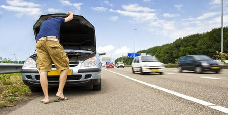 troubles: Man staring down at the engine of his stalled car on the hard shoulder of a motorway