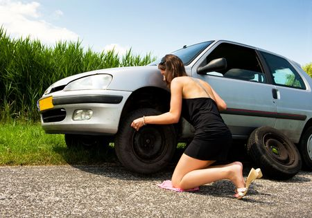 summer tire: Young woman, kneeling to tighten the bolts on a spare tire