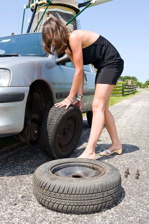 Young woman changing a flat tire  photo