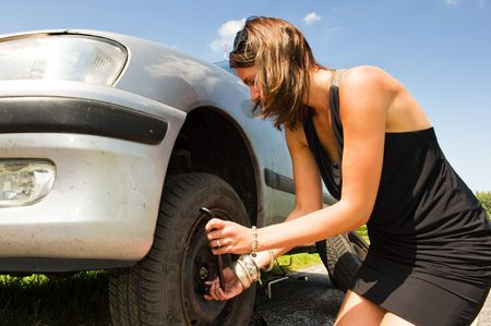 Young woman changing a flat tire on her car photo