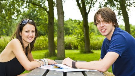 Young couple planning a trip at a picknick table, smiling at the camera