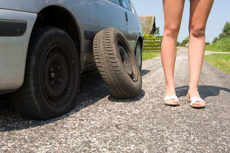 Long legged woman standing next to her car with a flat tire, the spare waiting to be put on photo