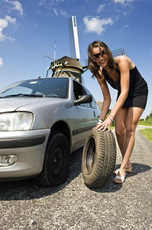 falda corta: Mujer joven, segura, cambiar una rueda pinchada en su coche por una carretera rural con un molino de viento en el backgrounc  Foto de archivo