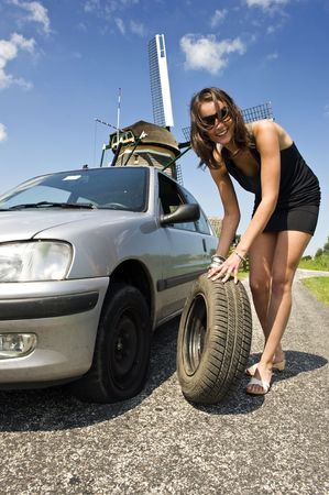 summer tire: Young, confident woman, changing a flat tire on her car on a rural road with a wind mill in the backgrounc Stock Photo
