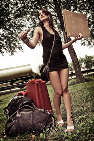 Young woman with a lot of luggage, trying to get a ride by hitchiking. Stock Photo - 6483987
