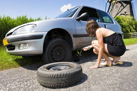 summer tire: Young woman jacking up her car to change a flat tire with a spare one