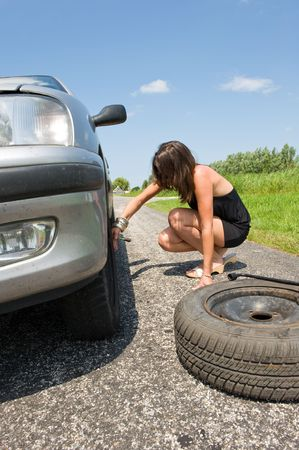 Young woman jacking up her car to change a flat tire with a spare one photo