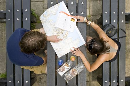picknick: Young couple planning a trip on a map, with a guide book on a picknick table, with pastries and soda bottles