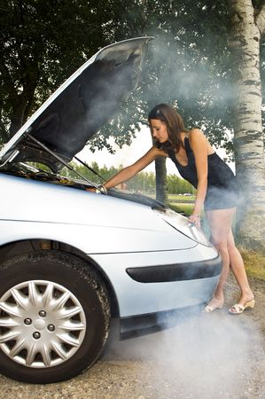 summer tire: A young woman, looking under the hood of her car to see whats wrong with her engine