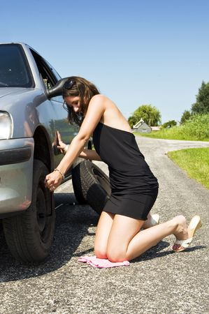 Young woman tightening the wheel nuts on a small rural road photo