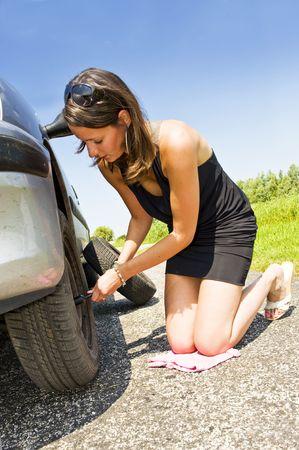 donna in ginocchio: Giovane donna inginocchiata, cambiando il pneumatico anteriore della sua auto  Archivio Fotografico