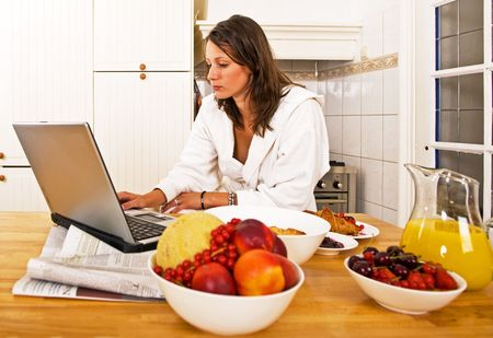 jus: Young woman, catching up with the days events on her laptop whilst drinking a glass of orange jus Stock Photo