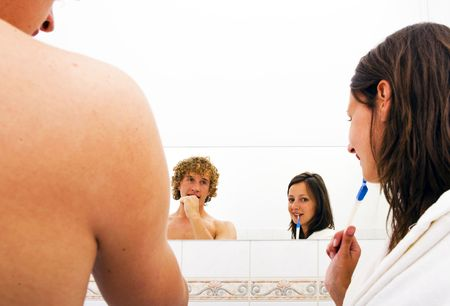 A couple brushing teeth together in a bathroom looking into the mirror. The man is looking at his girlfriend, the woman is looking at the camera Stock Photo - 6492615