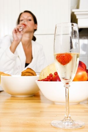 Champagne flute with a strawberry in it and a pretty brunette woman faintly in the background, representing a champagne breakfast on valentines day photo