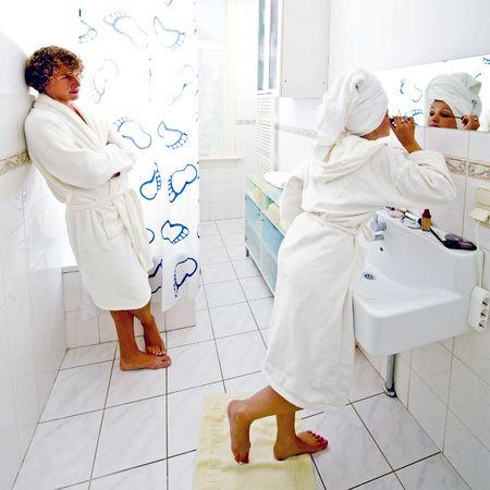 rituales: Los rituales de la ma�ana de un par, compartiendo el mismo cuarto de ba�o. Un hombre esperando con impaciencia su novia terminar de poner su maquillaje  Foto de archivo
