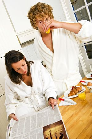 Young couple reading the paper on a casual morning breakfast in the kitchen photo