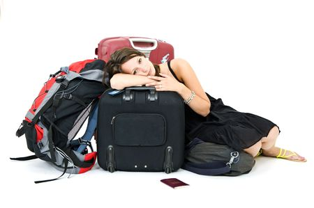 Young woman resting on her luggage, weary from travelling photo