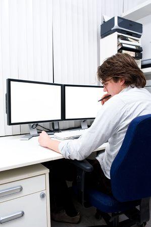 Un jeune designer à mâcher sa plume dans les pensées, assis derrière un poste de travail informatique.